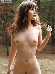 CStunning brown-eyed babe has a walk in the coniferous wood and poses nude among green pines and spruces.